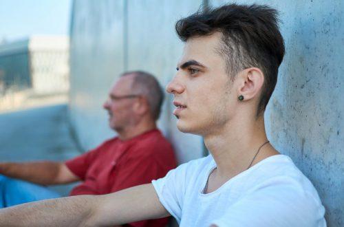 Ein ältere Mann und ein junger Mann sitzen nebeneinander an eine Wand gelenht im Freien und schauen nachdenklich in die Ferne.
